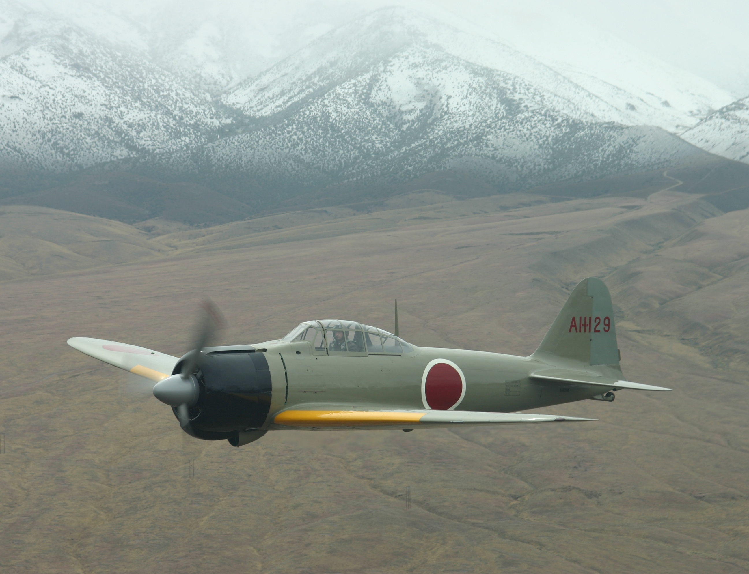 A perfectly preserved Mitsubishi A6M Zero aircraft flown near towering mountain peaks
